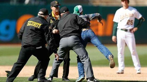 Umpire de la MLB derriba a fanático en medio de partido