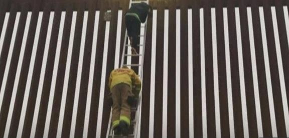 Rescatan a migrante arriba del muro fronterizo